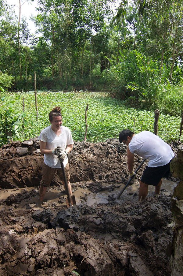 Colleen helps dig a trench for a new, sustainable biogas fuel system in Hoa An, Vietnam.