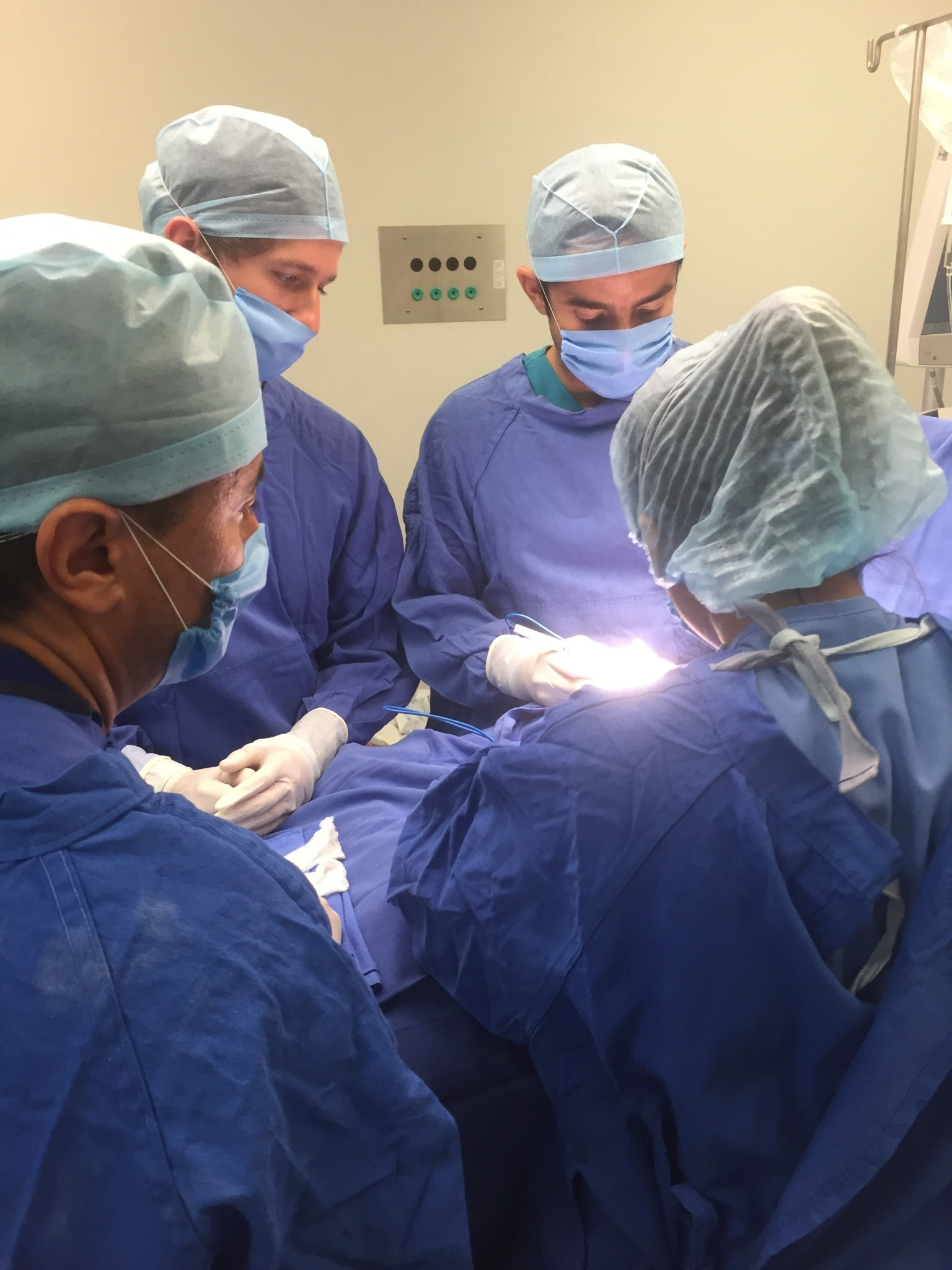 Surgical team in blue scrubs., doing surgery.