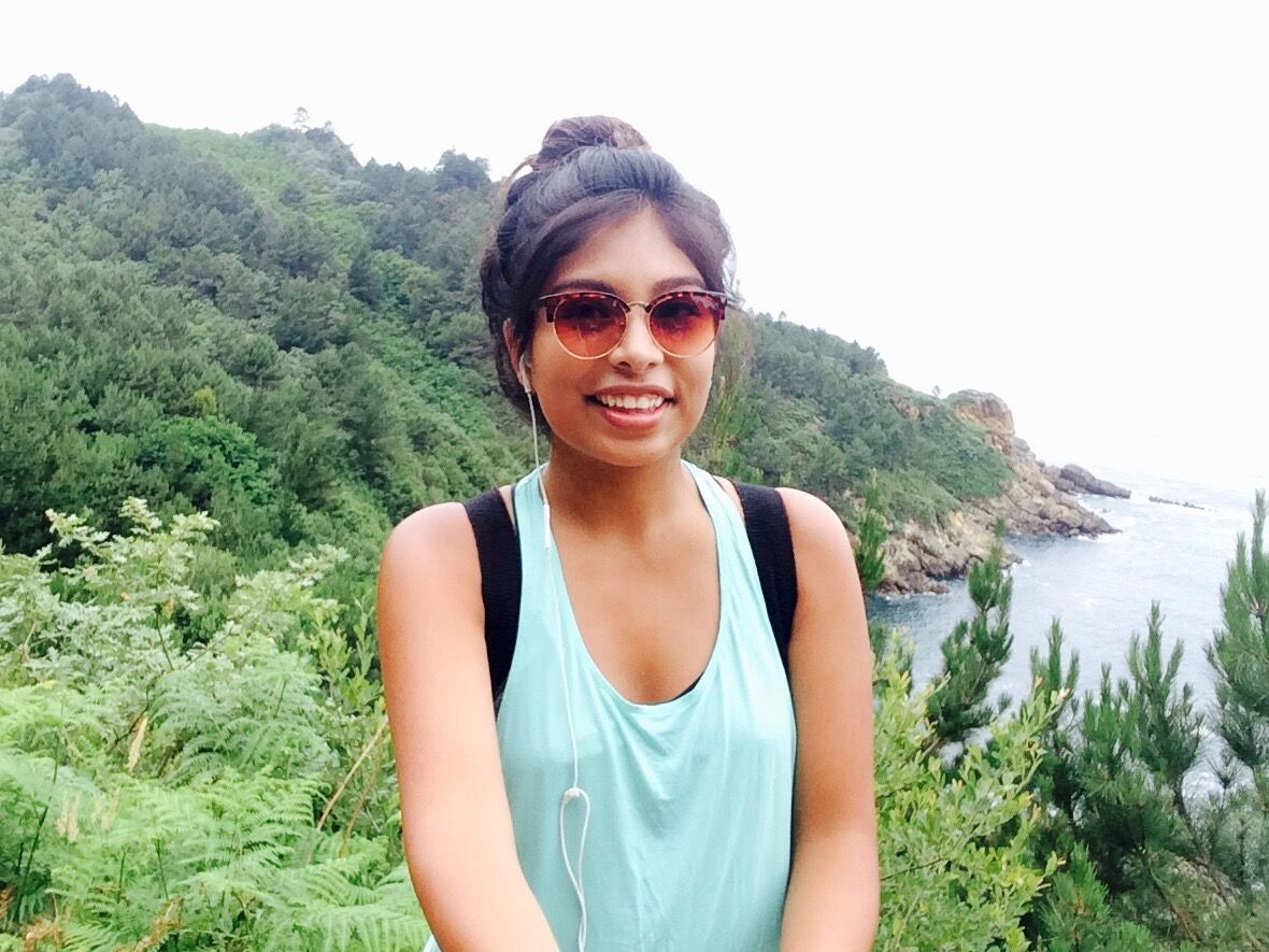 Young woman with sunglasses and backpack, pictured in coastal area.