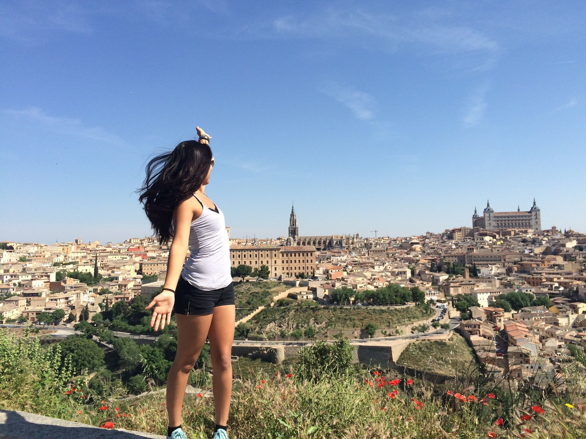 Photo of young woman gesturing towards historic Spanish city.
