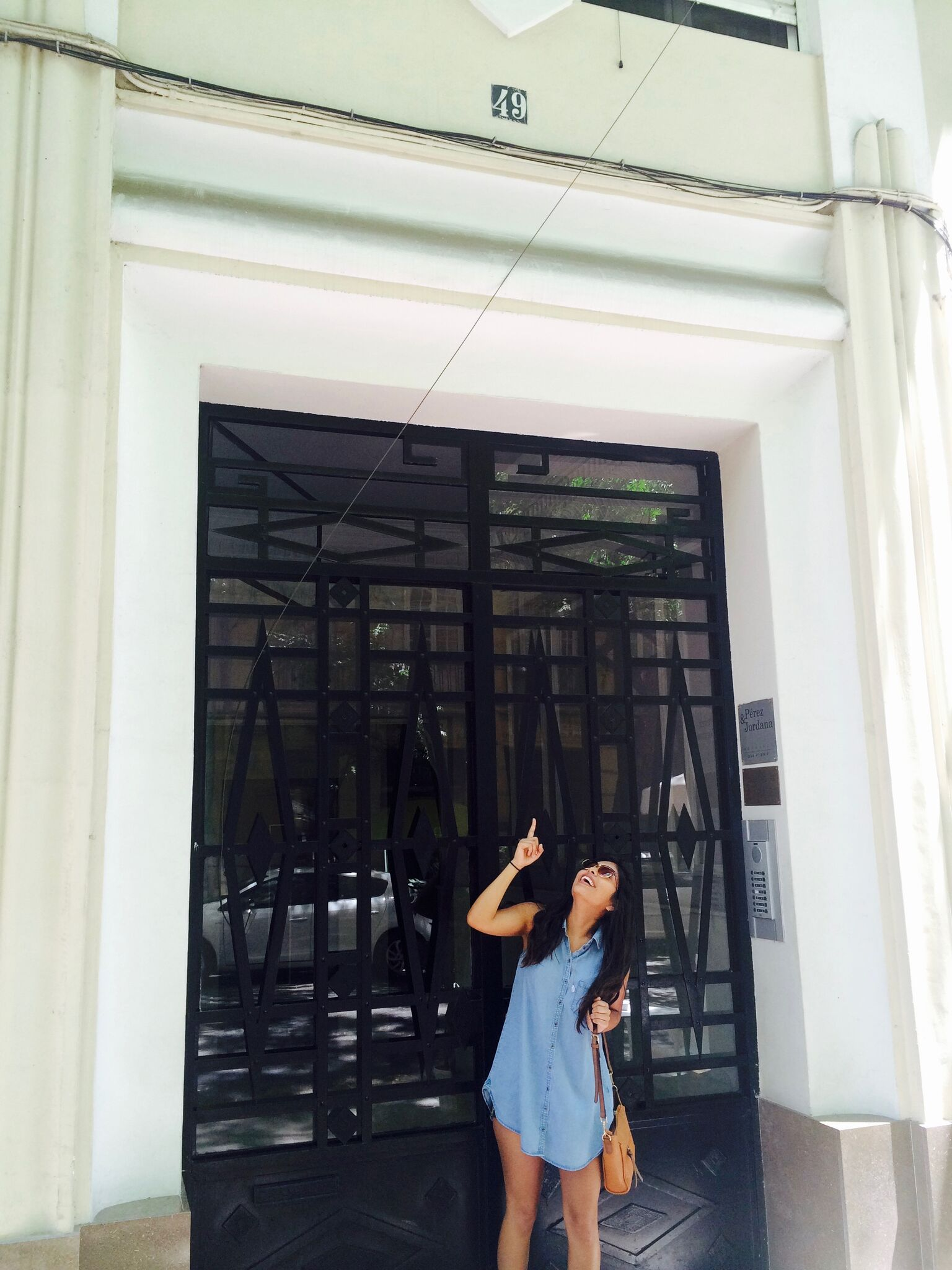 Young woman in front of an imposing doorway.