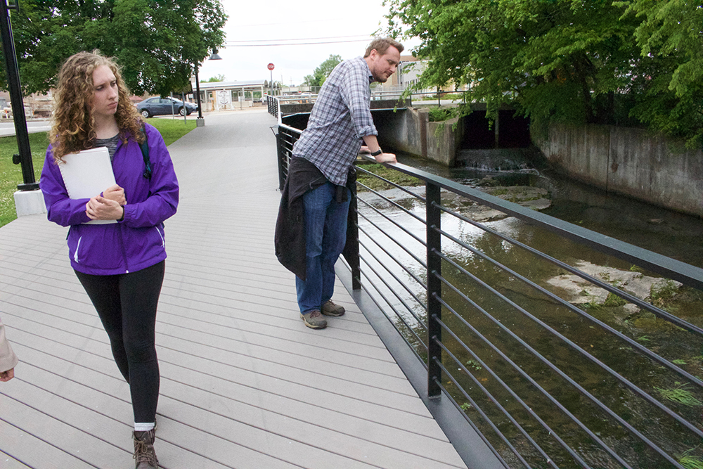 Professor and student examine a creek that runs through downtown.