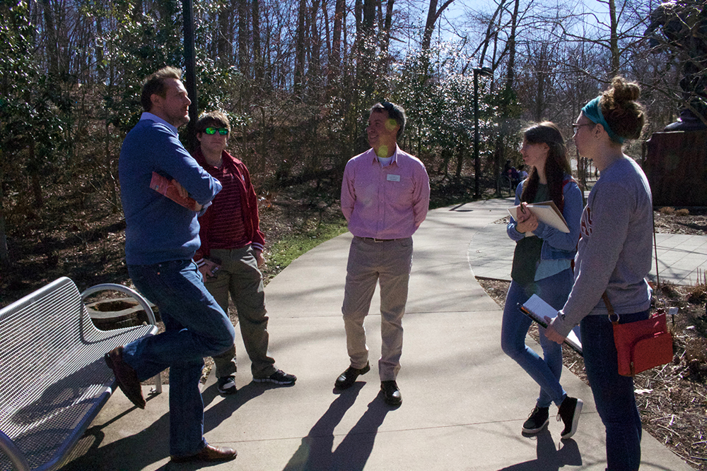 Professor and students on the trail, visit with landscape designer.