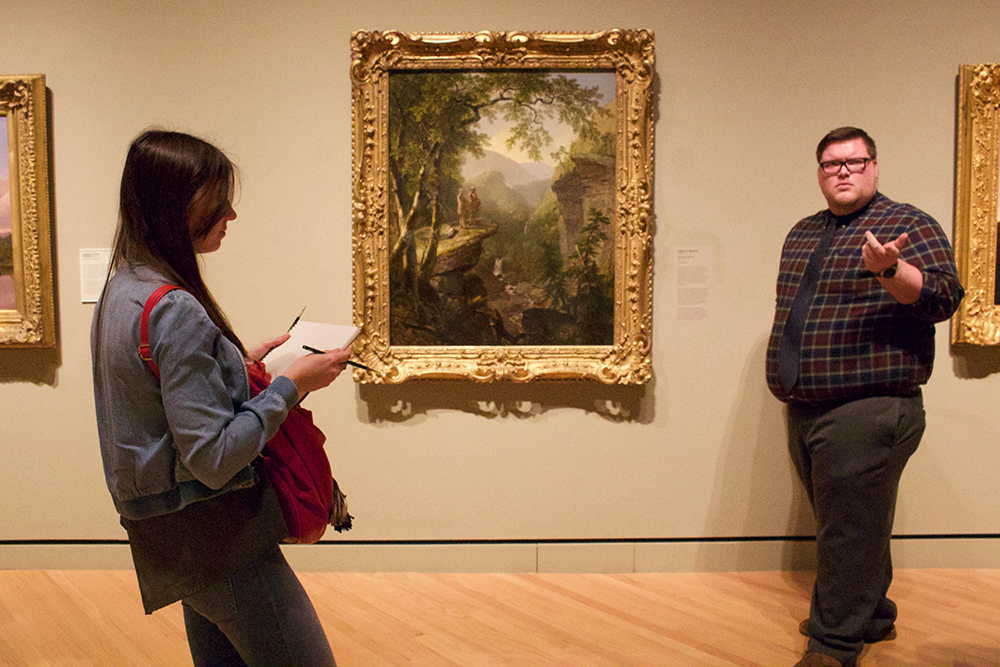 Docent discusses landscape painting while student sketches.