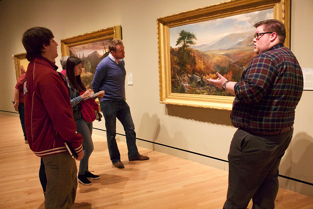 Professor, students and docent examine another landscape painting.