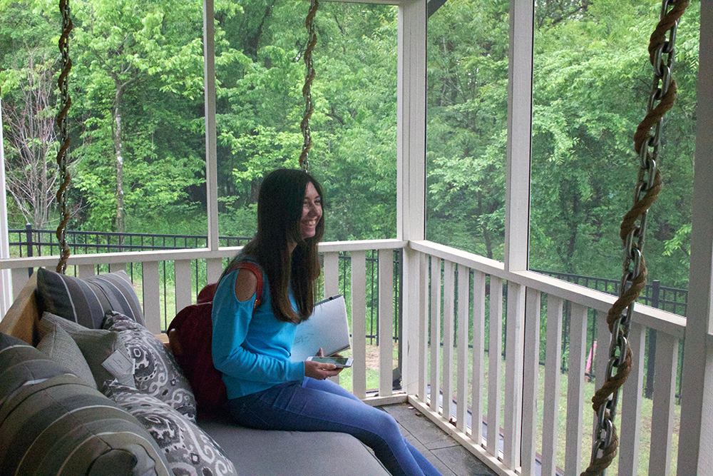 Student sits on a porch swing installed on a screened porch.