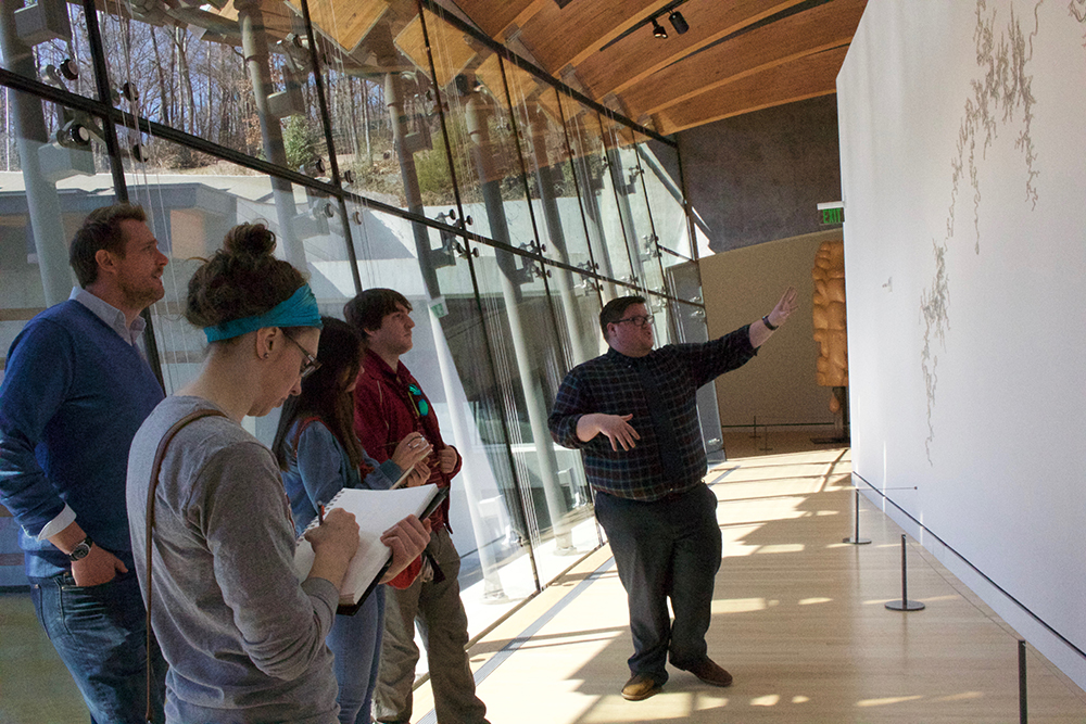 Professor, students and docent examine a sculpture installation.