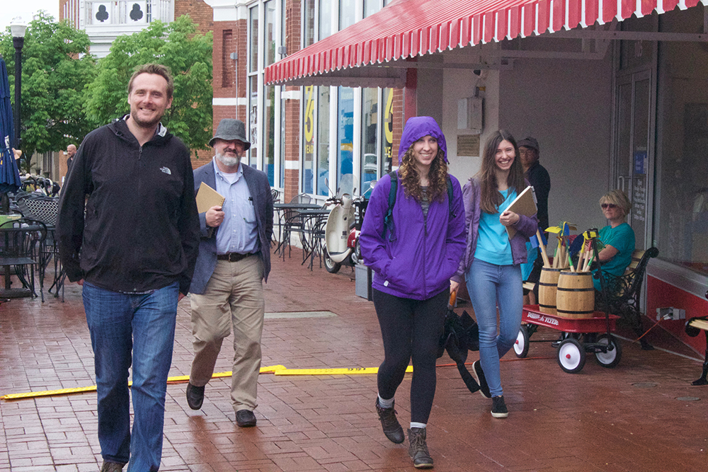 Students, professor and architect stroll in rainy downtown.