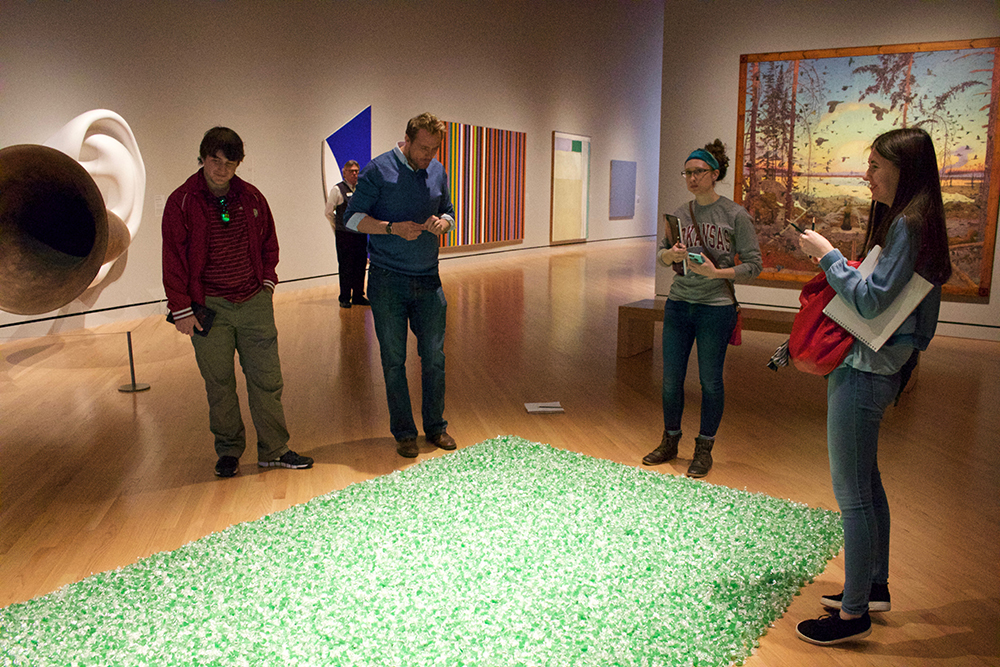 Professor and students examine a work of art consisting of a large square on floor filled in with candy.