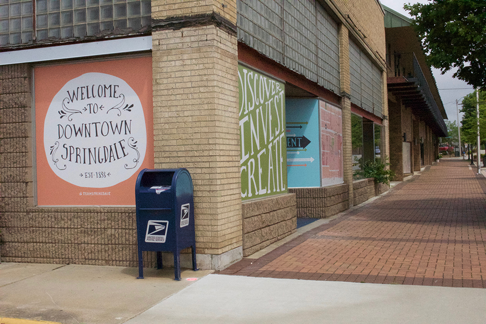 "Empty downtown with ""Welcome to Springdale"" sign painted on building."