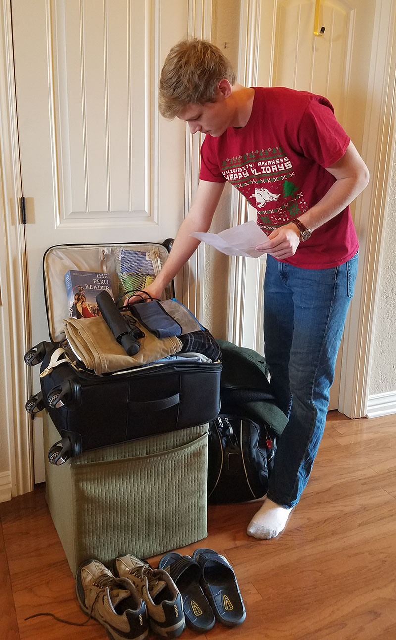 Student packs small suitcase.