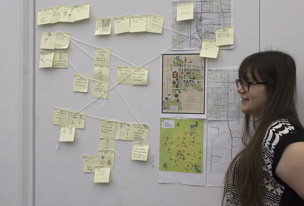 Woman standing by board of post-it notes and maps.