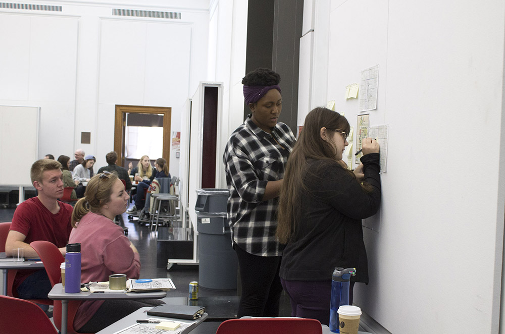 Two women write on whiteboard while two classmates look on.