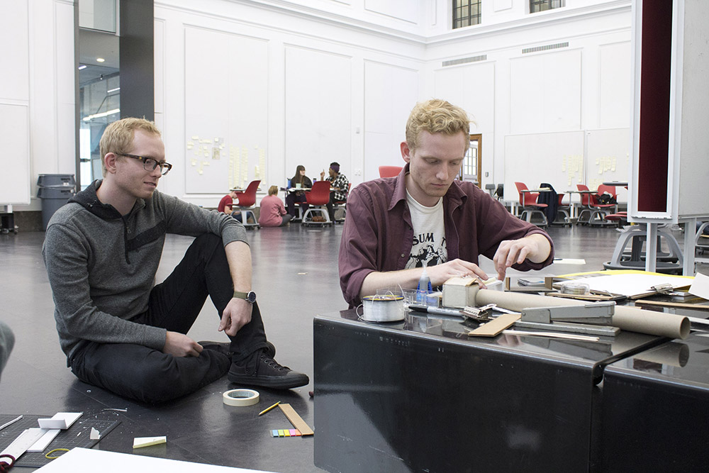 Two men sitting on floor amid design materials and tools.