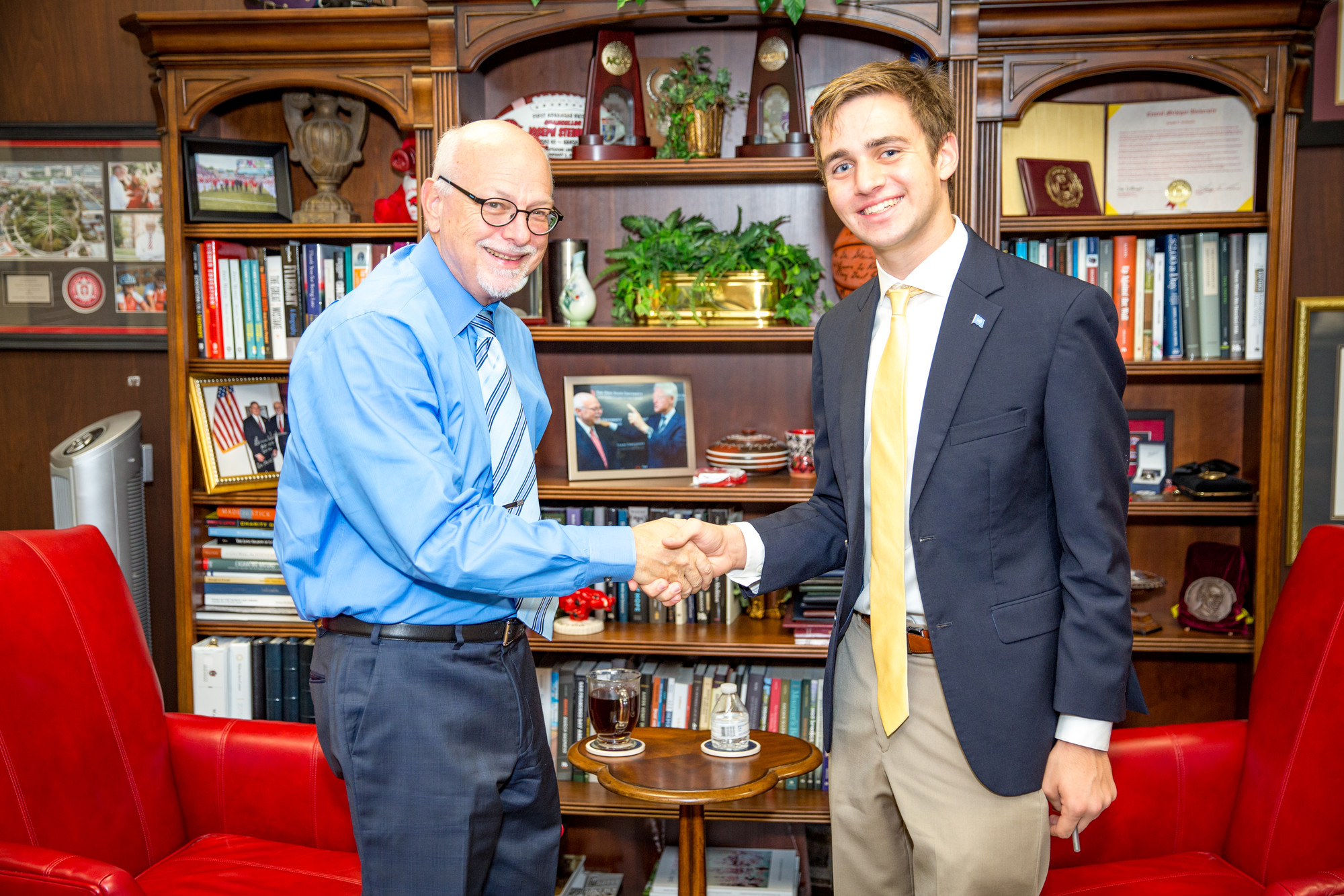 Chancellor shakes student dean's hand.