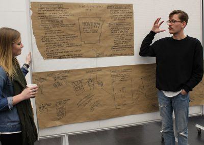 "11: Sloan Aulgur and Riley Garret summarize ideas developed by the transportation team. In addition to the app that would allow homeless folks to hit a button and hail a ride that's paid for, they explored the idea of combining the Razorback and Ozark Regional Transit bus routes, expanding routes and running times, and redesigning bus stops to foster interaction and connection. They also proposed capitalizing on the area's growing hike and bike trail system by leading a ""bike drive"" and offering lessons on bicycle maintenance through the U of A's HPER center."