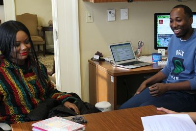 Mentor and student chat in an office.