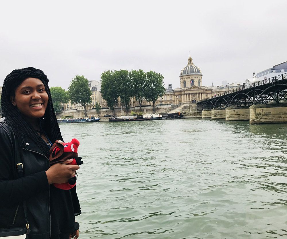 Photo of young woman holding stuffed hog, beside the Seine in Paris.