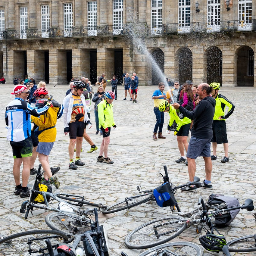 Cyclists celebrate their arrival in Santiago de Compostela with champagne.