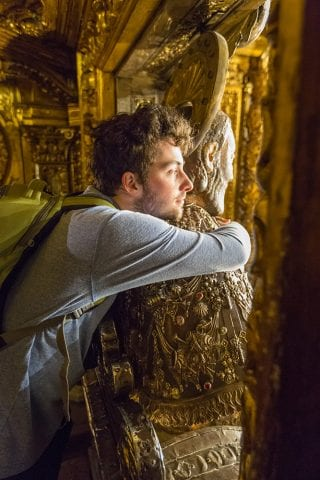 A young man hugs the gilded statue of St. James in the Cathedral at Santiago de Compostela