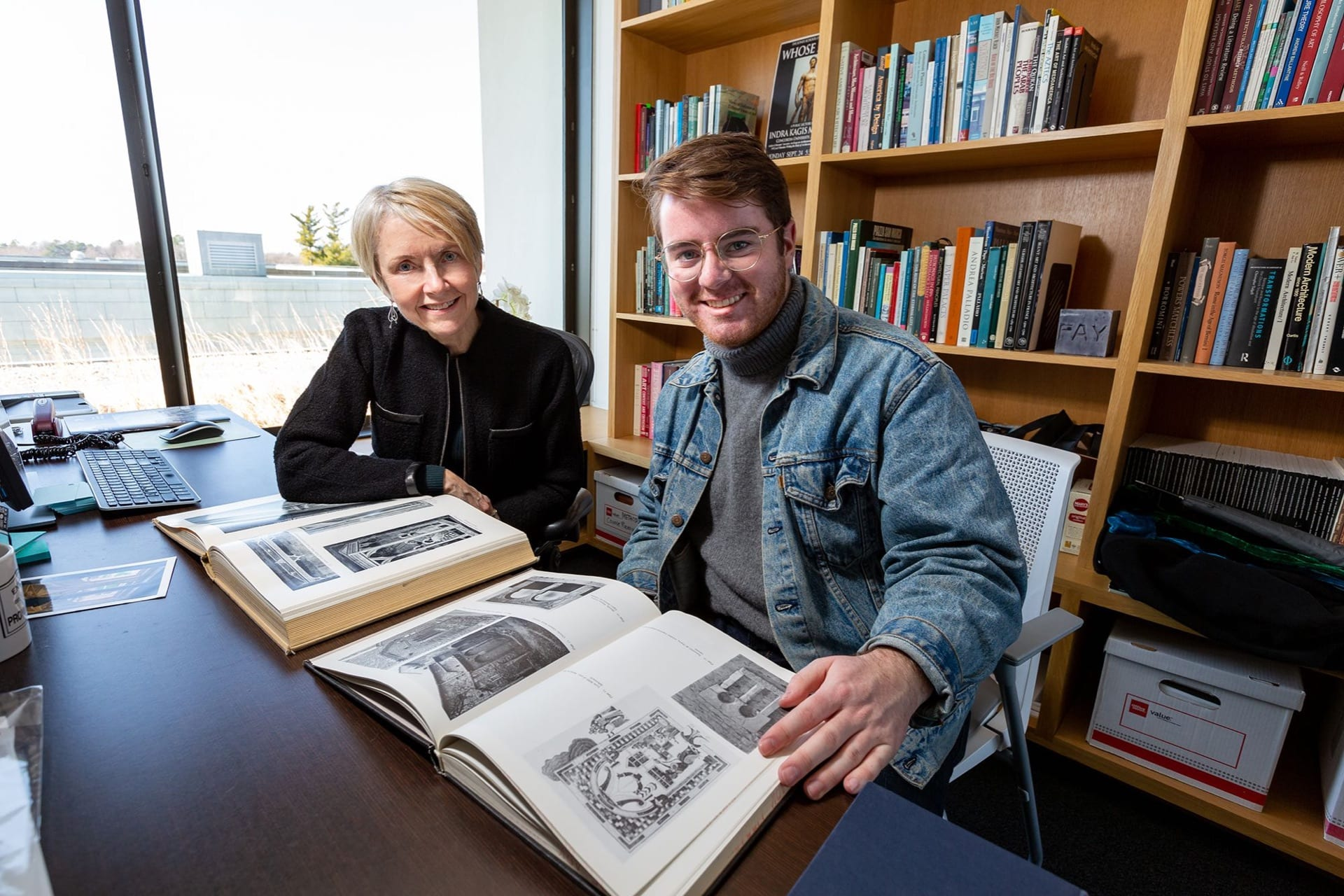 Female professor and male student look at art books in her office.