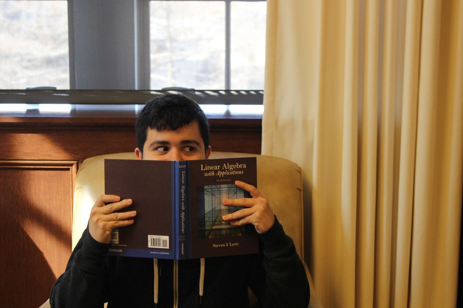 Student hides behind linear algebra textbook.