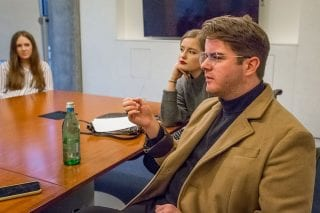 Three students are seated around a boardroom table.
