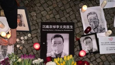 Candles and flowers are placed beside photo of doctor Li Wenliang