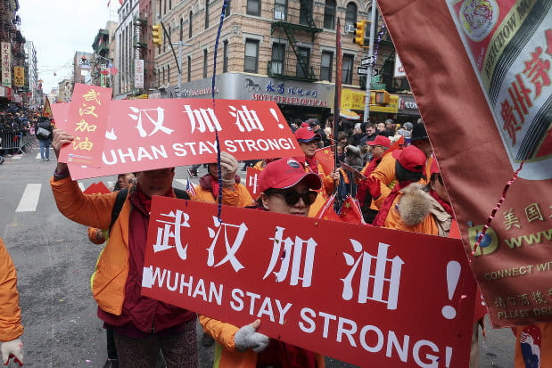 """Chinese workers march with banners saying """"Wuhan Stay Strong!"""""""