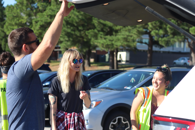 Three students at their cars talking