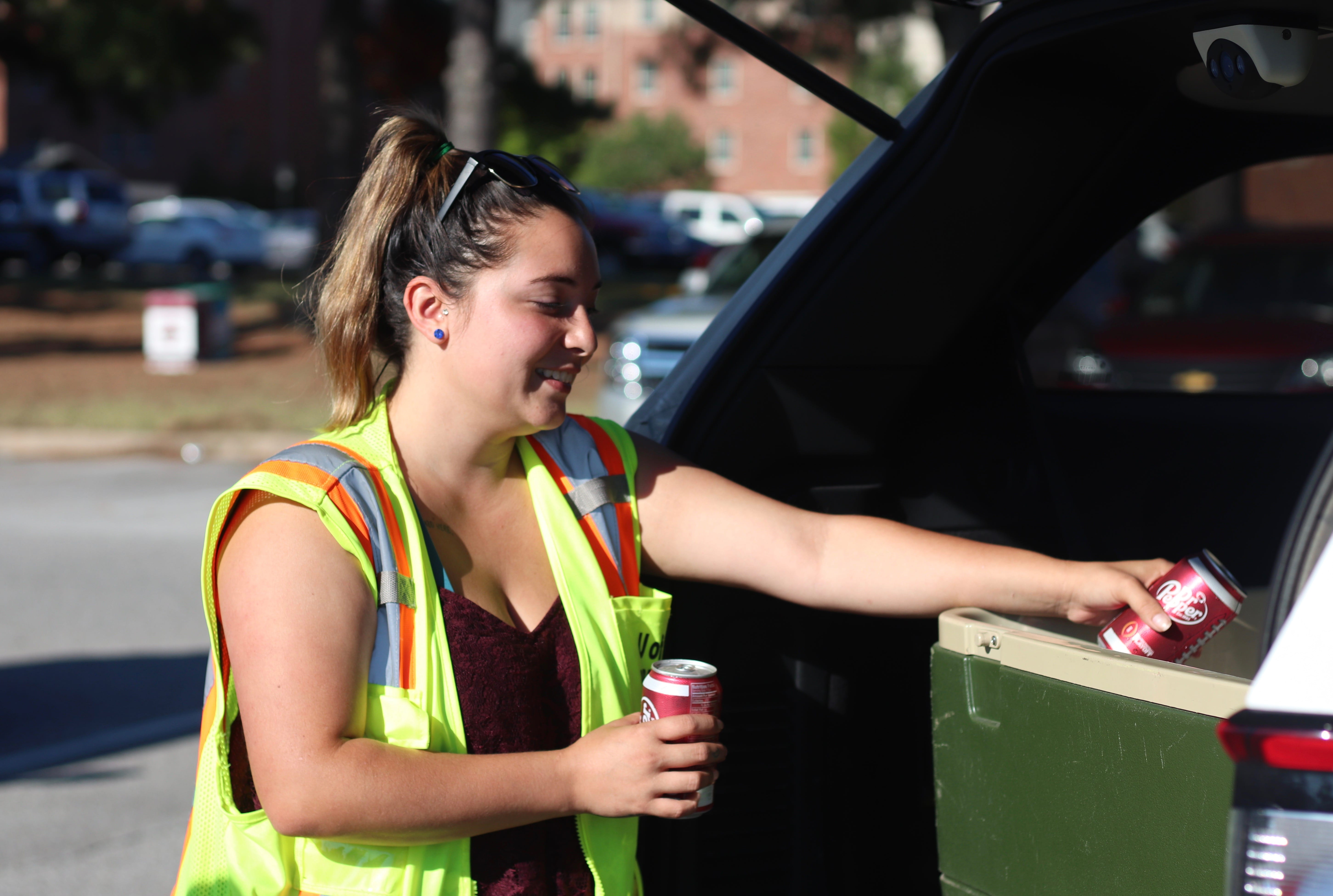 A parking employee getting a soda from a cooler
