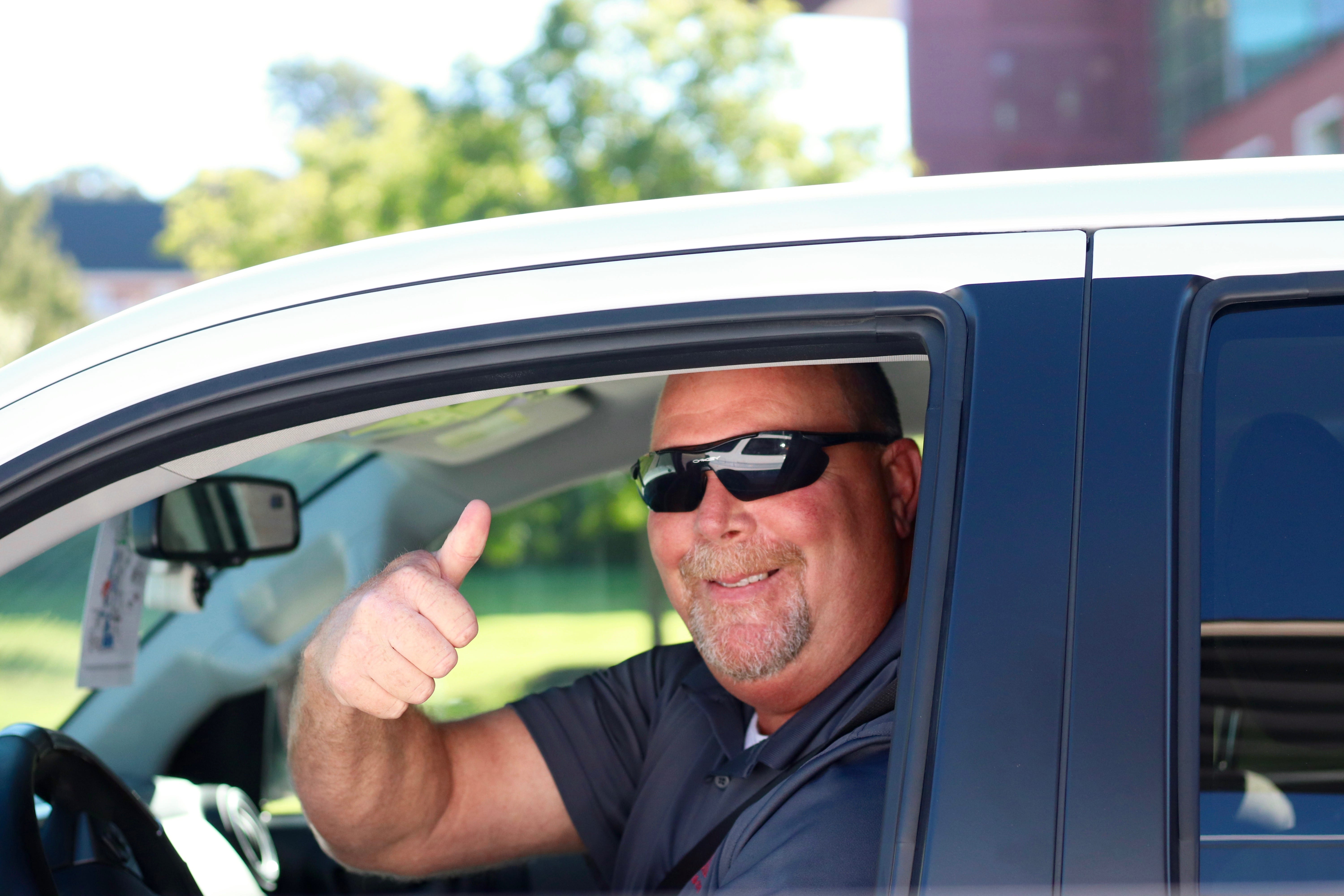 A man with sunglasses smiling and giving a thumbs up from the front seat of his car