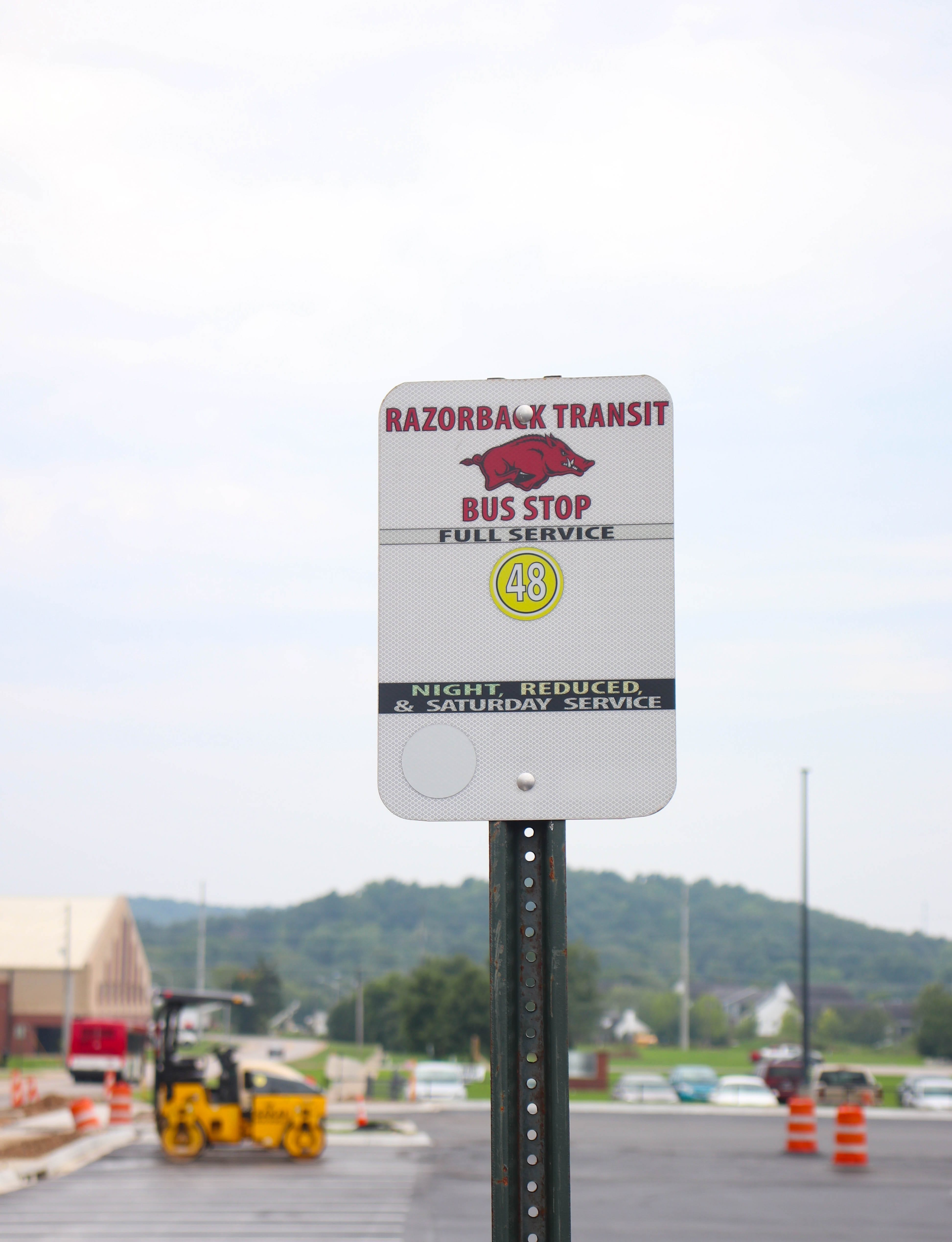"""A sign that reads """"Razorback Transit Bus Stop, Full Service Route 48"""""""