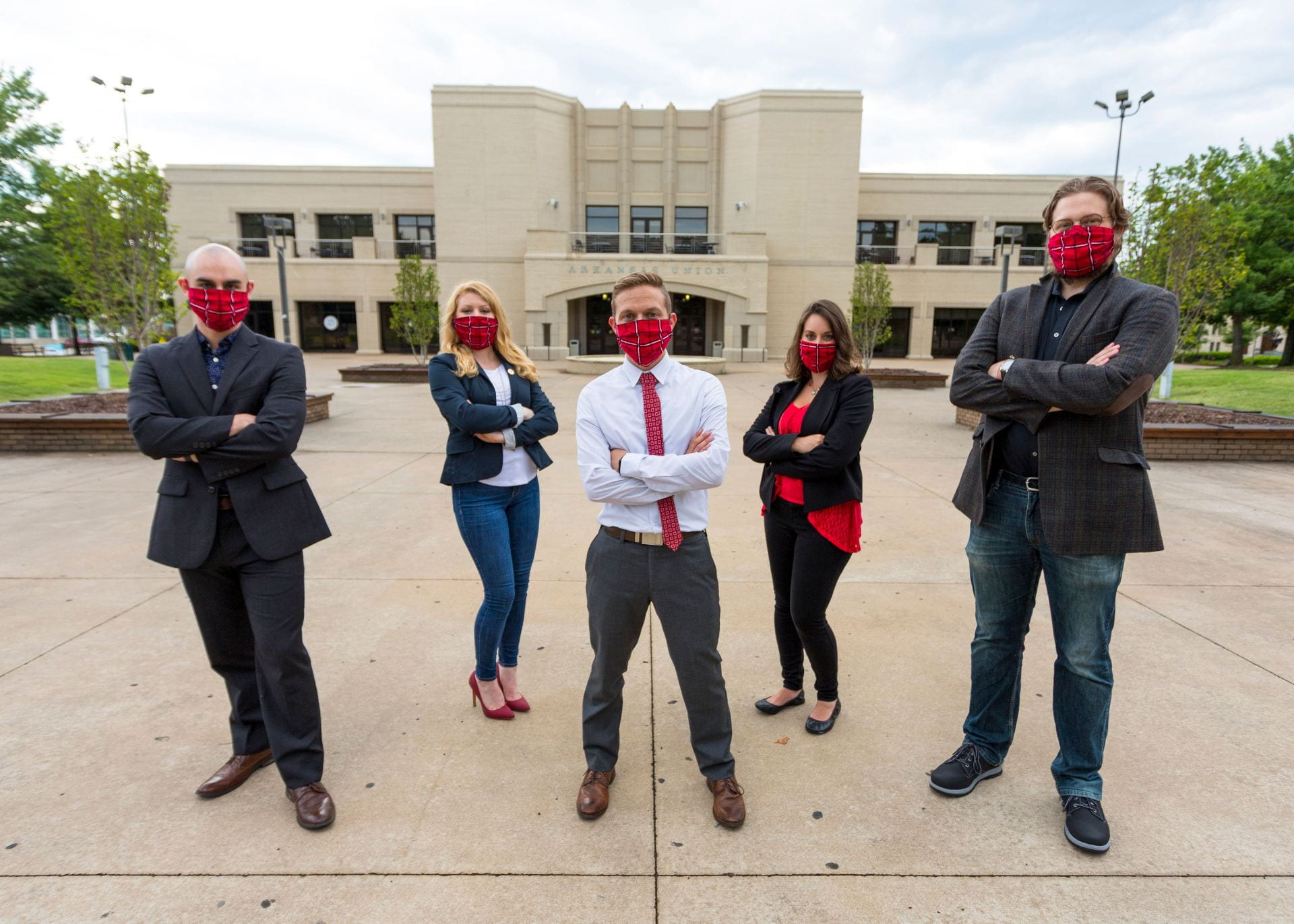 The five members of the GPSC Executive Council (DiLoreto-Hill, Dzurilla, Holdier, Bonney, and Slank), all wearing PPE face masks w/ the Razorback logo, stand distanced with arms crossed in front of the Arkansas Student Union.