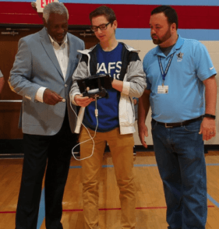 Image of three people gathered in a gym and looking at the controls for a drone.