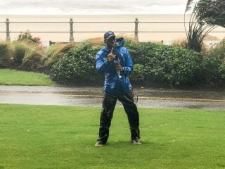 Tevin Wooten speaking on air of The Weather Channel during a storm with a beach line and ocean in the background.