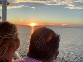 Two people looking out over the sunset from a cruise ship