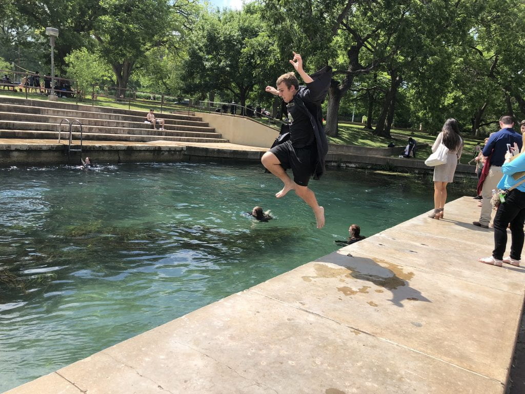 B.S. Chemist Steven Gralinski celebrates with the Texas State tradition of jumping into the San Marcos River after graduation
