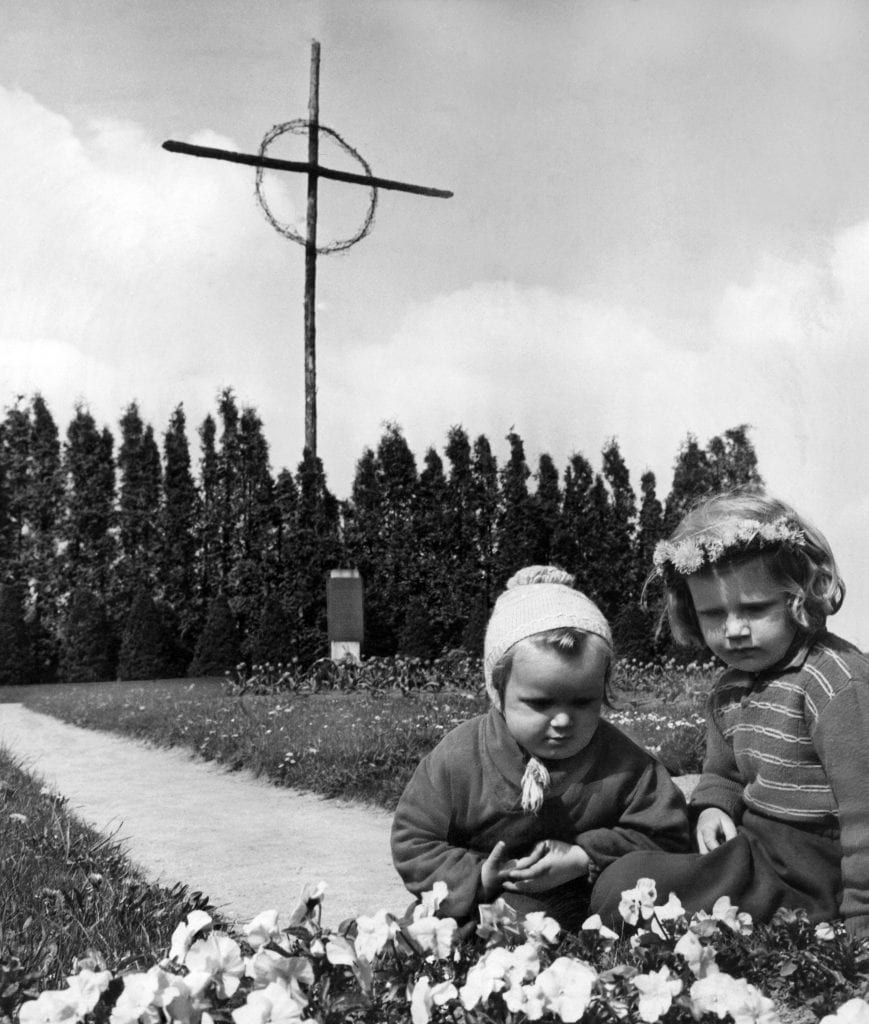 Children at the cemetery of Lidice, Czechoslovakia, on May 20, 1957, where the victims of the 1942 destruction of the village by Nazi troops are buried. The tall cross in the background is said to have been made from the charred beams of Lidice farm houses. (AP Photo/Czech News Agency)