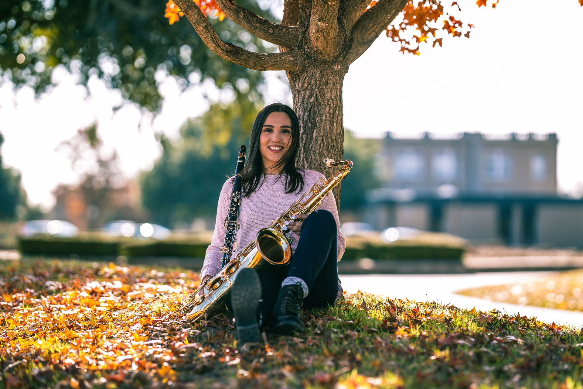 TXST Alum Lizzy Mora sitting under a tree holding a clarinet and a tenor saxophone