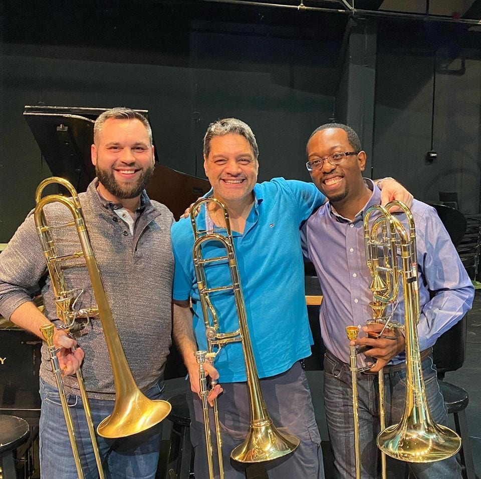 Three trombonists standing together, smiling for the camera.
