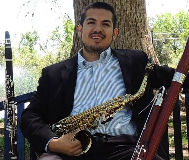 Josue Mora sitting on a bench with an alto saxophone and bassoon