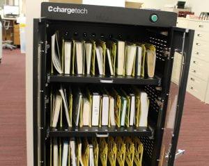 books lined up on shelves of UV sanitizing machine