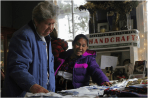 Celia Santiz assists a festival attendee in picking out an item.