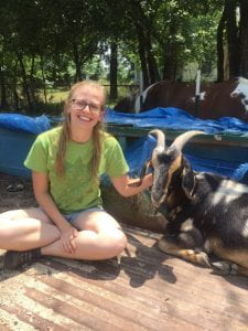 Annie, the mother goat, and I sit together in the bed of an out-of-commission truck. Goats act a lot like dogs; Annie wags her tail when she is excited to see someone, and loves affection.