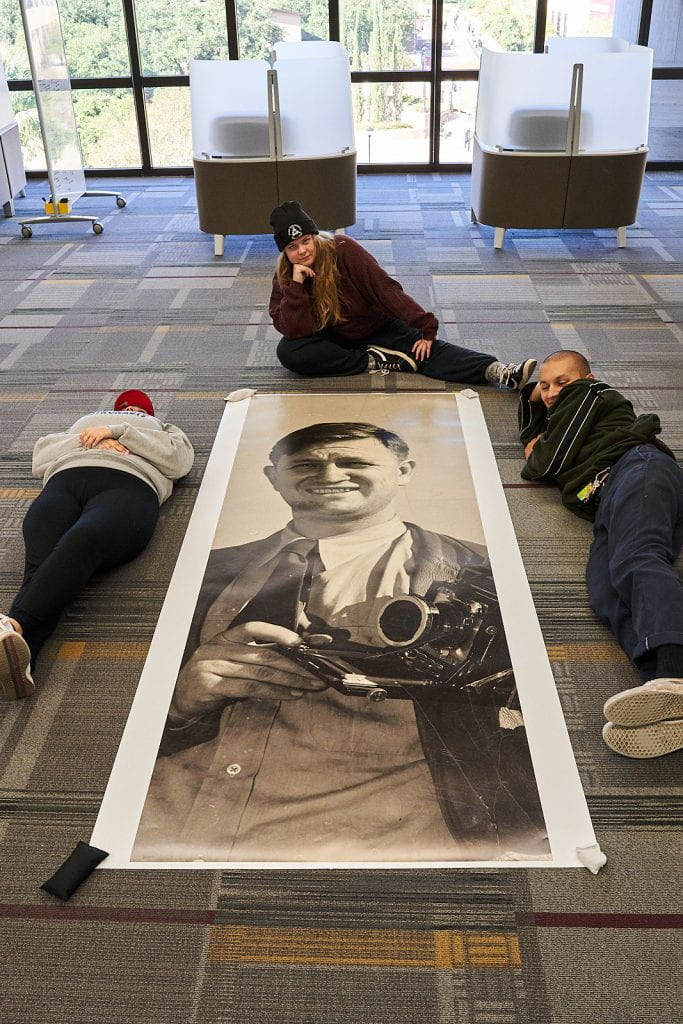 Two students on side and one student sitting above a long, narrow print on the floor