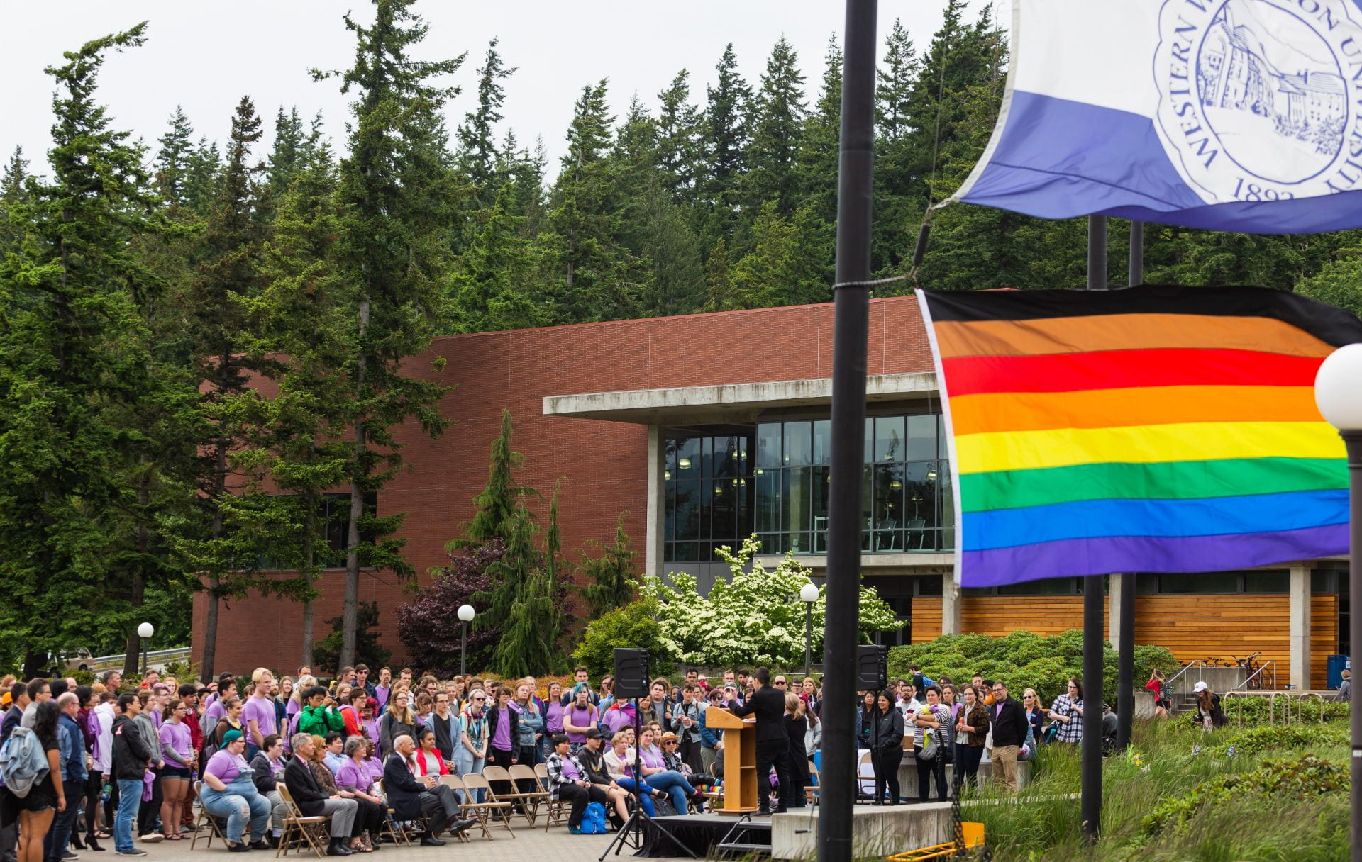 Group of people standing outside at Pride Celebration in front of flags near Rec Center, listening to speaker at podium. Pride flag in foreground.