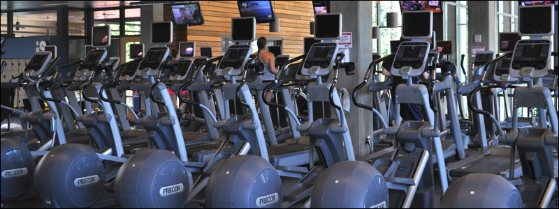A row of eliptical machines stand ready for use in the upper cardio area of the Rec Center