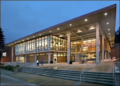 Front exterior of Wade King Recreation Center at dusk with lights on