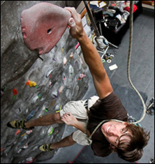 Rock climber on belay hangs by one hand from a hold near the top of the wall